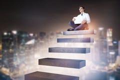 Homem de negócios que senta-se em escadas no céu da cidade da noite foto de stock
