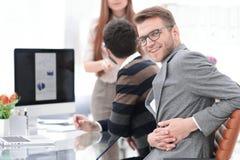 Homem de negócios que senta-se em sua mesa no escritório fotografia de stock royalty free