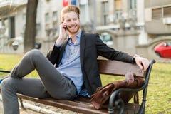 Homem de negócios que senta-se em um banco de parque ao falar no telefone fotografia de stock royalty free