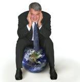 Homem de negócios que senta-se em um globo imagens de stock royalty free