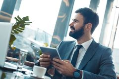 Homem de negócios que senta-se em um restaurante do centro de negócios que guarda a tabuleta digital que olha para fora a janela imagens de stock