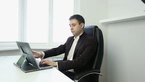 Homem de negócios que senta-se em uma cadeira do escritório na tabela e que datilografa no portátil de prata filme