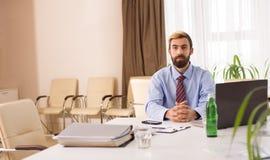 Homem de negócios que senta-se em uma mesa com portátil Foto de Stock