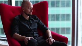 Homem de negócios que senta-se em uma poltrona vermelha em seu escritório filme