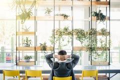 Homem de negócios que senta-se na cadeira da parte traseira sobre o fundo da sala do escritório imagem de stock royalty free