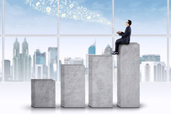 Homem de negócios que senta-se na carta a mais alta Imagens de Stock