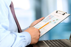 Homem de negócios que senta-se na frente do portátil, analisando dados na GR Imagens de Stock