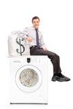 Homem de negócios que senta-se na máquina de lavar completamente do dinheiro foto de stock