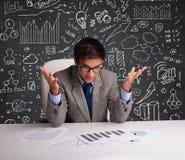 Homem de negócios que senta-se na mesa com esquema e ícones do negócio Imagem de Stock Royalty Free