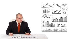 Homem de negócios que senta-se na mesa com estatísticas e gráficos fotografia de stock