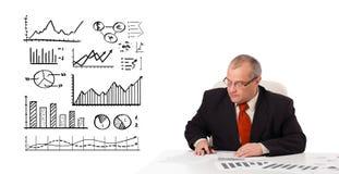 Homem de negócios que senta-se na mesa com estatísticas e gráficos imagens de stock