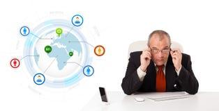 Homem de negócios que senta-se na mesa com um globo e uns ícones sociais foto de stock