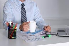 Homem de negócios que senta-se na mesa de escritório que tem uma ruptura de café Fotografia de Stock Royalty Free