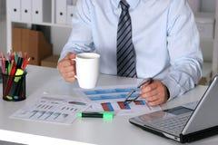 Homem de negócios que senta-se na mesa de escritório que tem uma ruptura de café Fotos de Stock Royalty Free