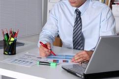 Homem de negócios que senta-se na mesa de escritório que tem uma ruptura de café Foto de Stock Royalty Free