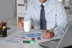 Homem de negócios que senta-se na mesa de escritório que tem uma ruptura de café e que guarda uma caneca Imagem de Stock Royalty Free