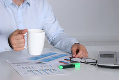 Homem de negócios que senta-se na mesa de escritório que tem uma ruptura de café e que guarda uma caneca Fotografia de Stock