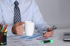 Homem de negócios que senta-se na mesa de escritório que tem uma ruptura de café e que guarda uma caneca Foto de Stock