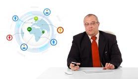 Homem de negócios que senta-se na mesa e que guarda um telefone celular com globo fotografia de stock
