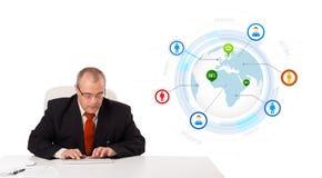 Homem de negócios que senta-se na mesa e que datilografa no teclado com o globo Imagem de Stock