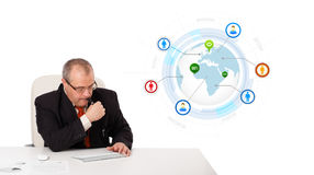 Homem de negócios que senta-se na mesa e que datilografa no teclado com o globo imagem de stock royalty free