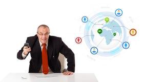 Homem de negócios que senta-se na mesa e que guarda um telefone celular com globo foto de stock royalty free