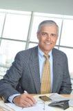Homem de negócios que senta-se na mesa no ajuste do escritório Imagem de Stock