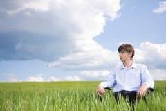 Homem de negócios que senta-se na pastagem sob o céu azul Imagens de Stock Royalty Free