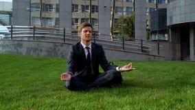 Homem de negócios que senta-se na posição de lótus, meditando sobre o gramado perto do centro do escritório imagens de stock royalty free