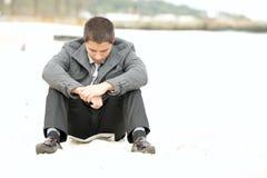 Homem de negócios que senta-se na praia comprimida Fotografia de Stock Royalty Free