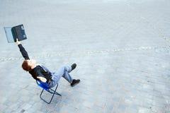 Homem de negócios que senta-se na rua Fotografia de Stock