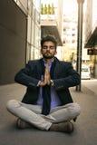 Homem de negócios que senta-se na rua da estrada e na ioga praticando Sp imagens de stock royalty free