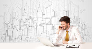 Homem de negócios que senta-se na tabela branca com construções tiradas mão Fotografia de Stock Royalty Free