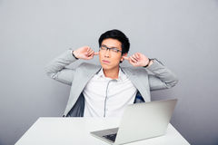 Homem de negócios que senta-se na tabela e que cobre suas orelhas imagem de stock royalty free