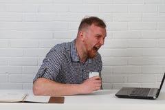 Homem de negócios que senta-se na tabela e que trabalha no computador Resolve tarefas importantes do negócio É bem sucedido e wel Fotos de Stock Royalty Free