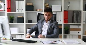 Homem de negócios que senta-se na tabela no escritório branco e nas mãos de jogo atrás da cabeça que balança na escritório-cadeir