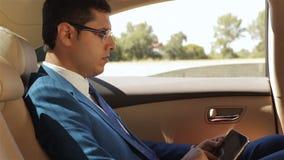 Homem de negócios que senta-se na tabuleta da leitura do carro video estoque