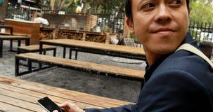 Homem de negócios que senta-se no banco no café exterior 4k video estoque