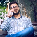 Homem de negócios que senta-se no banco de parque com café usando o telefone celular fotografia de stock
