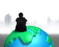 Homem de negócios que senta-se no globo do mapa 3d que olha a cidade cinzenta das construções Fotos de Stock