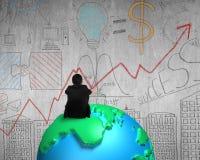 Homem de negócios que senta-se no globo do mapa 3d que olha wal concreto da garatuja Fotografia de Stock