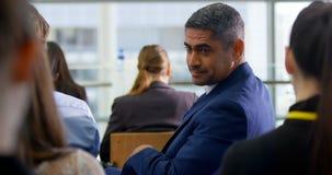 Homem de negócios que senta-se no seminário 4k do negócio video estoque