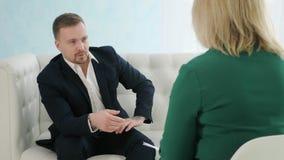 Homem de negócios que senta-se no sofá que fala ao psicólogo fêmea