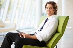 Homem de negócios que senta-se no sofá no escritório usando a tabuleta de Digitas imagem de stock
