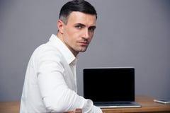 Homem de negócios que senta-se no thet capaz com a tela vazia do portátil Fotos de Stock