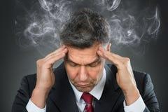 Homem de negócios que sofre da dor de cabeça fotografia de stock royalty free