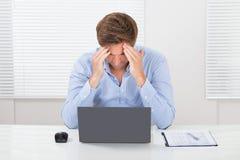Homem de negócios que sofre da dor de cabeça foto de stock royalty free
