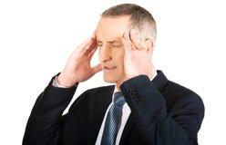 Homem de negócios que sofre da dor de cabeça Fotografia de Stock