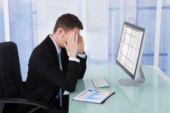 Homem de negócios que sofre da dor de cabeça na mesa do computador imagem de stock