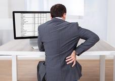 Homem de negócios que sofre da dor lombar ao sentar-se na mesa fotografia de stock royalty free